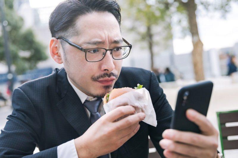 携帯を見ながらハンバーガーを食べる男性