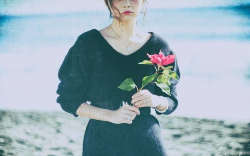 一輪の花を持つ女性