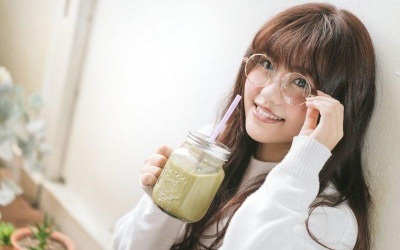 スムージーを飲んで微笑む女性