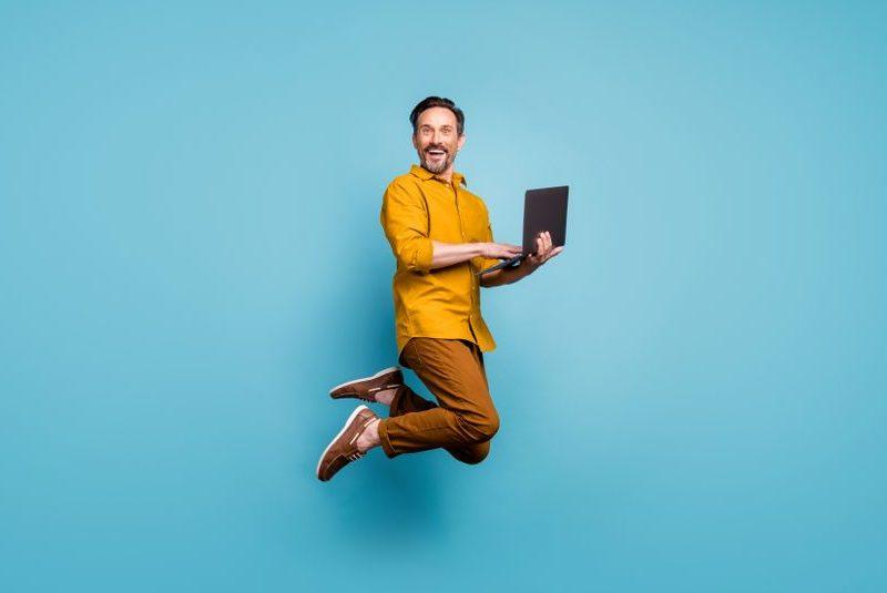パソコンを持ってジャンプ