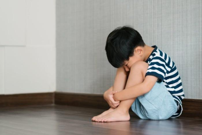 膝を抱える子供