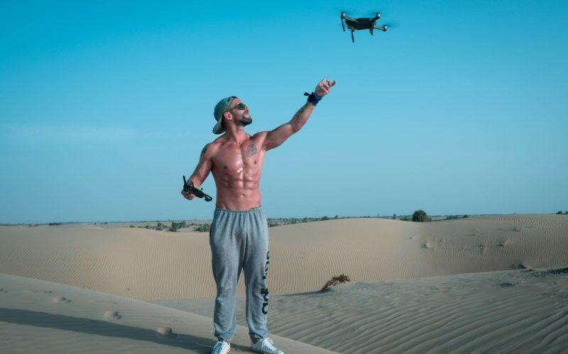 砂漠でドローンをあげる男